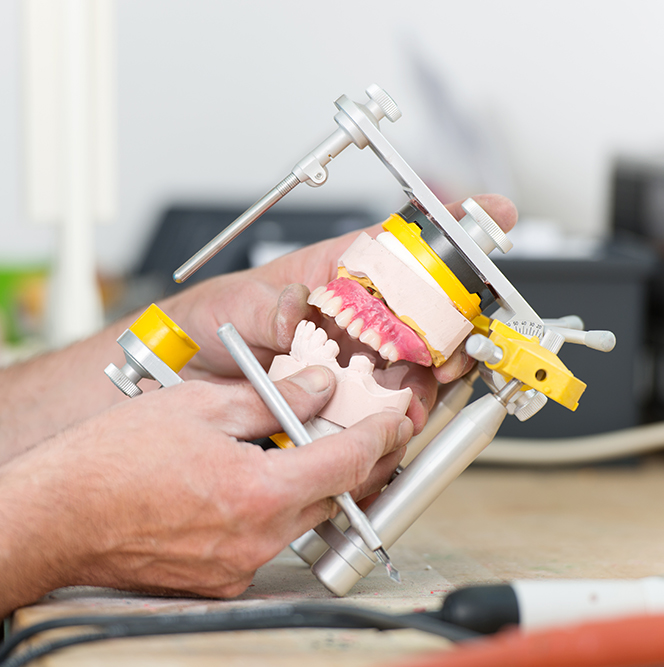 Technician's Hands Working With Articulator In Dental Laboratory